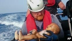 Un membre de l'équipage de l'organisation humanitaire Sea-Watch porte un bébé migrant noyé, dont le corps a été repêché au cours d'une opération de sauvetage au large des côtes de la Libye, 27 mai 2016. (Christian Buttner / EIKON NORD GMBH ALLEMAGNE via AP)
