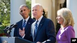 Biden, Xaaskiisa iyo Obama oo taagan beerta Rose ee aqalka cad oo uu go'aankiisa kaga dhawaaqay.