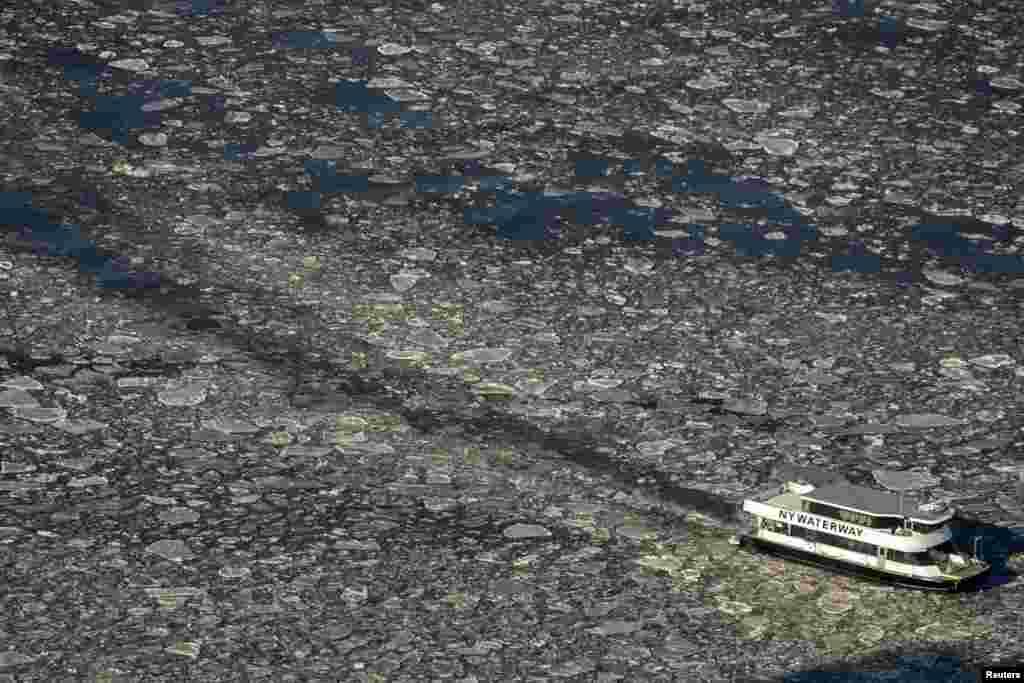 Sebuah kapal ferry meluncur di sungai Hudson antara New Jersey dan Manhattan, New York yang membeku akibat udara dingin.