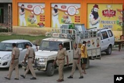 FILE - Indian policemen walk in front of a store belonging to Dera Sacha Sauda sect chief Gurmeet Ram Rahim Singh after it was sealed by authorities, near Sonipat, India, Aug. 26, 2017.