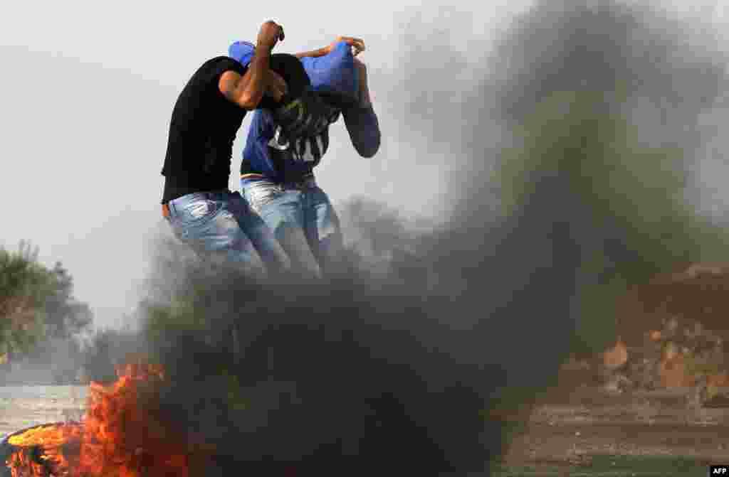 19일 이스라엘군의 공격에 얼굴을 가린 팔레스타인 대학생 시위대.