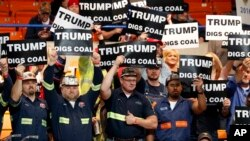 Coal miners, a constituency Democratic presidential contender Hillary Clinton has also been courting, wave Trump signs as they wait for a rally in Charleston, W.Va., May 5, 2016.