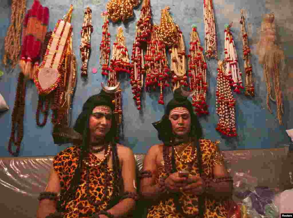 Artists dressed as the Hindu Lord Shiva read a message on a mobile phone as they prepare to participate in a religious procession ahead of the Mahashivratri festival in Jammu, Nepal. Hindu women across the country celebrate Mahashivratri, better known as Lord Shiva's wedding anniversary, so that their husbands will be blessed with long lives.