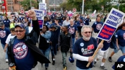 Members and family of unions walk in the annual Labor Day parade in Detroit, Monday, Sept. 5, 2011. (AP Photo/Paul Sancya)