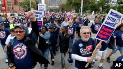 FILE - Members and family of unions walk in the annual Labor Day parade in Detroit.. (AP Photo/Paul Sancya)