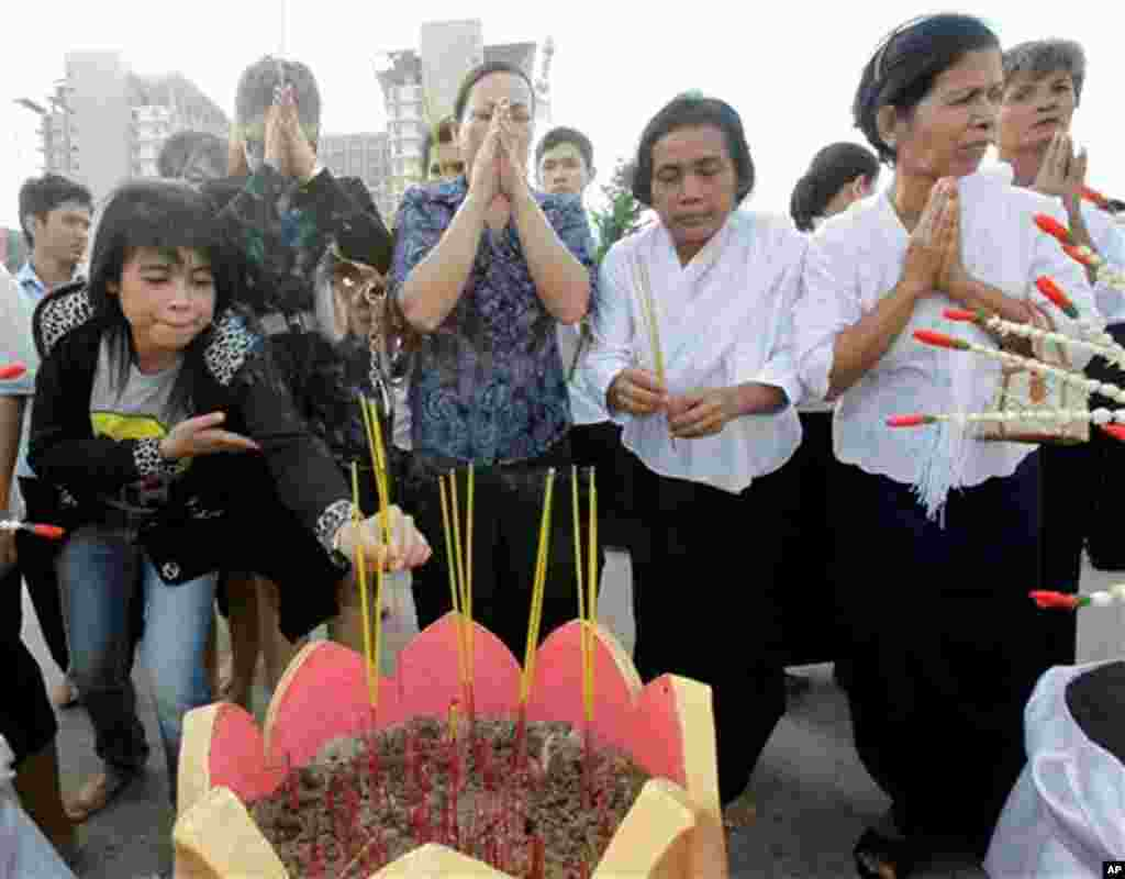 Cambodian women offer prayer during a memorial service Thursday, Nov. 25, 2010, near a bridge where hundreds of festival goers were killed Monday in a stampede in Phnom Penh, Cambodia. Cambodia began a day of mourning Thursday with the prime minister weep