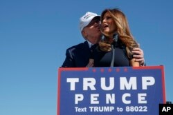 FILE - Republican presidential candidate Donald Trump kisses his wife, Melania, during a campaign rally in Wilmington, N.C., Nov. 5, 2016.