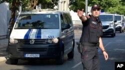 Policajac usmerava kolonu koja prevozi optužene za pokušaj puča u Crnoj Gori, Podgorica, 20. jul 2017. godine (Foto: AP/Risto Božović)
