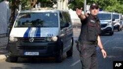 Policajac u Podgorici usmerava kolonu policijskih vozila koja prevoze osumnjilčene za državni udar u oktobru 2016. (Foto: AP/Risto Božović)
