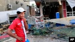 一名男子在視察巴格達一個居民區在汽車炸彈爆炸後的情況