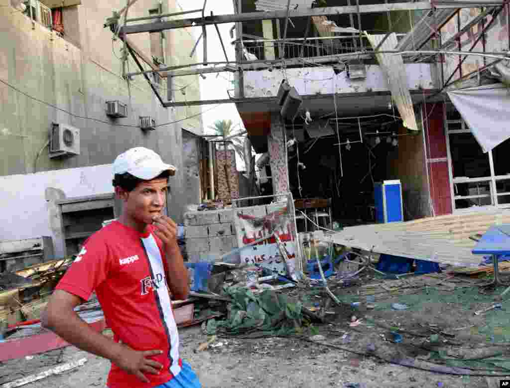 A man inspects the aftermath of a car bomb attack in Karrada, Baghdad, Sept. 4, 2013.