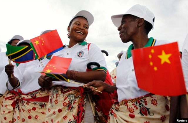 FILE - Tanzanian women wait to welcome China's President Xi Jinping when he disembarks at Julius Nyerere International Airport.