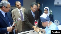 Egyptian Tourism Minister Hisham Zaazou (L) and South Korea's Consul to Egypt Lim Wan Shun (C) hand flowers to a South Korean tourist who was injured in a blast on a bus in Taba, at a hospital in Sharm El-Sheik hospital, southern Sinai, Feb. 17, 2014.