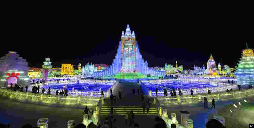 在黑龙江哈尔滨,国际冰雪节上彩色灯光辉映下的彩色广场建筑冰雕(2014年1月8日)。哈尔滨靠近寒冷的西伯利亚,冬天最低温度可降至零下35摄氏度以下。