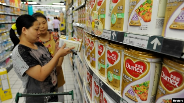 A sales assistant (back) helps a customer to select Dumex milk powder at a supermarket in Hefei, Anhui province, August 5, 2013.