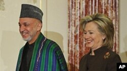 U.S. Secretary of State Hillary Clinton and Afghan President Hamid Karzai arrive for the opening of the US-Afghanistan bilateral discussions at the Department of State, 11 May 2010