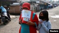 Seorang ibu dan anaknya mengenakan masker wajah untuk melindungi dari penularan virus corona (Covid-19) di Depok, 13 April 2020. (Foto: Reuters)