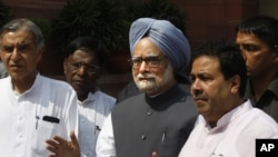 Indian Prime Minister Manmohan Singh, center, talks to the media in New Delhi, August 8, 2012.