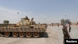 Un combattant kurde tient son arme près d'un char dans le quartier de Ghwairan à Hasaka, en Syrie, le 22 août 2016.