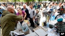FILE - Volunteers share food and water for residents in the town of Luhansk, eastern Ukraine, Sept. 14, 2014
