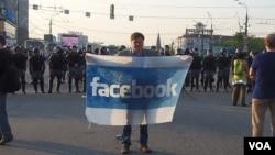 社交網站已成為俄羅斯和烏克蘭民眾串聯上街抗議的主要工具。在去年普京就職總統前夕的5月6日莫斯科大規模反政府抗議中,一名示威者在防爆警察前手持臉書旗幟。(美國之音 白樺拍攝)
