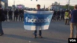 社交网站已成为俄罗斯和乌克兰民众串联上街抗议的主要工具。在去年普京就职总统前夕的5月6日莫斯科大规模反政府抗议中,一名示威者在防爆警察前手持脸书旗帜。(美国之音 白桦拍摄)