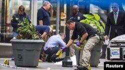 Un policía de Nueva York coloca marcas que establecen los casquillos del tiroteo frente al edificio Empire State, sobre la 5a. Avenida en Manhattan.