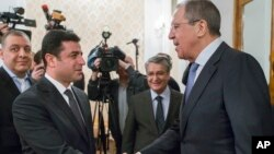 Russian Foreign Minister Sergey Lavrov, right, shakes hands with Co-chairman of pro-Kurdish People's Democratic Party, or HDP, Selahattin Demirtas prior to a meeting in Moscow, Russia, Dec. 23, 2015.