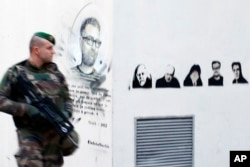A french soldier patrols next to a painting of killed cartoonists, Charb at left, and at right, Honore, Wolinski, Cabu, Charb and Tignous outside satirical newspaper Charlie Hebdo former office, one year after the attacks on it, in Paris, France, Jan. 7,