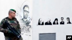 FILE - A french soldier patrols next to a painting of killed cartoonists, Charb at left, and at right, Honore, Wolinski, Cabu, Charb and Tignous outside satirical newspaper Charlie Hebdo former office, one year after the attacks on it, in Paris, France.