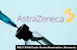 FILE PHOTO: A vial and sryinge are seen in front of a displayed AstraZeneca logo