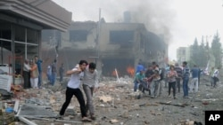 People carry injured people from one of explosion sites after several explosions killed at least 40 people and injured dozens in Reyhanli, near Turkey's border with Syria, May 11, 2013.
