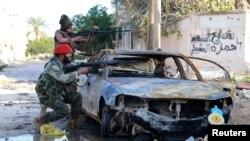 Tentara Libya pro-pemerintah mengarahkan senjatanya dalam bentrokan dengan pemberontak di Benghazi, Desember 2014.