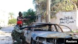 Pasukan pro-pemerintah Libya membidik senjata mereka dalam bentrokan dengan Dewan Shura Revolusioner Libya, aliansi man tan pemberontak anti-Gadhafi, yang bergabung dengan kelompok Islamis Ansar al-Sharia, di Benghazi, 28 Desember 2014.