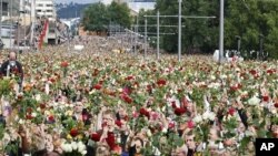 Masses of people holding roses take part in a memorial march outside Oslo City Hall, July 25, 2011
