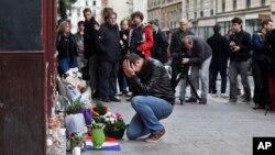 Một cư dân Paris khóc khi đặt hoa phía trước quán cà phê Carillon tại Paris, ngày 14/11/2015.