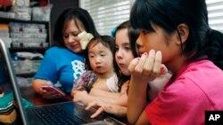 Perempuan keluarga Smith, dari kiri ke kanan, ibu Niki Smith, GiGi, 3, Macy Jade, 7 dan Guan Ya, 14, menggunakan Google Translate untuk berkomunikasi di rumah mereka di Mississippi. (AP/Rogelio V. Solis)