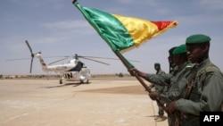 Des soldats maliens devant l'hélicoptère transportant le Premier ministre malien atterrit à Menaka, au Mali, le 9 mai 2018.