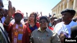 Morgan Tsvangirai, à gauche, chef du mouvement pour le changement démocratique du Zimbabwe (MDC), une main levée, marche aux côtés du leader du Zimbabwe People (ZIMPF), Joice Mujuru, ancien vice-président du Zimbabwe, lors d'une manifestation contre La mauvaise gestion de l'économie du président Robert Mugabe à Gweru, le 13 août 2016.