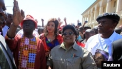 FILE - Morgan Tsvangirai, left, leader of Zimbabwe's main opposition Movement For Democratic Change, gestures next to Zimbabwe People Firstleader Joice Mujuru, center, who is a former Vice President of Zimbabwe, during a march against what protesters say is the mishandling of the economy by President Robert Mugabe's government in Gweru, Aug. 13, 2016.