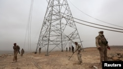 Soldiers loyal to Yemen's government search for landmines left by the Houthi rebels next to destroyed transmission towers in the Mas area, of Marib, Dec. 26, 2015.