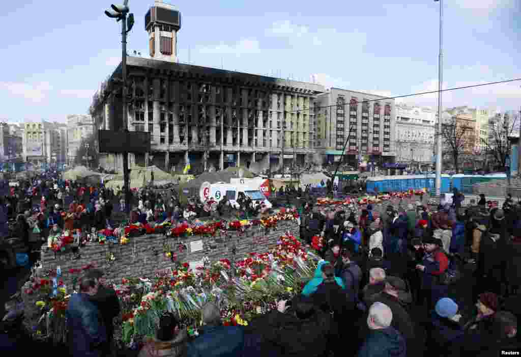 People lay flowers at the barricades in memory of the victims of the recent clashes in central Kyiv, Feb. 24, 2014.