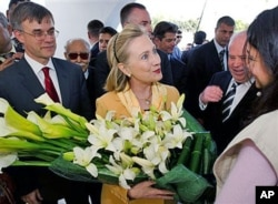 FILE - Then-U.S. Secretary of State Hillary Clinton is presented flowers as she tours the Red Crescent with then-U.S. Ambassador to Tunisia Gordon Grey, left, in Tunis, March, 17, 2011.