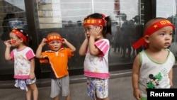 """资料照片:北京奥运会开幕式当天,头戴""""中国加油""""标语的幼儿在天安门广场附近。(2008年8月8日)"""