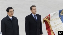 French President Nicolas Sarkozy, right, and Chinese President Hu Jintao, salute the French flag, shortly after the arrival of Hu Jintao at Paris Orly airport Thursday Nov. 4, 2010. Chinese President Hu Jintao is on a two-day state visit in France.(AP Pho