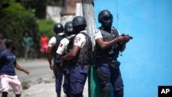 Police officers with their weapons drawn search for suspects in the killing of Haiti's President Jovenel Moise, in Port-au-Prince, Haiti, July 8, 2021.