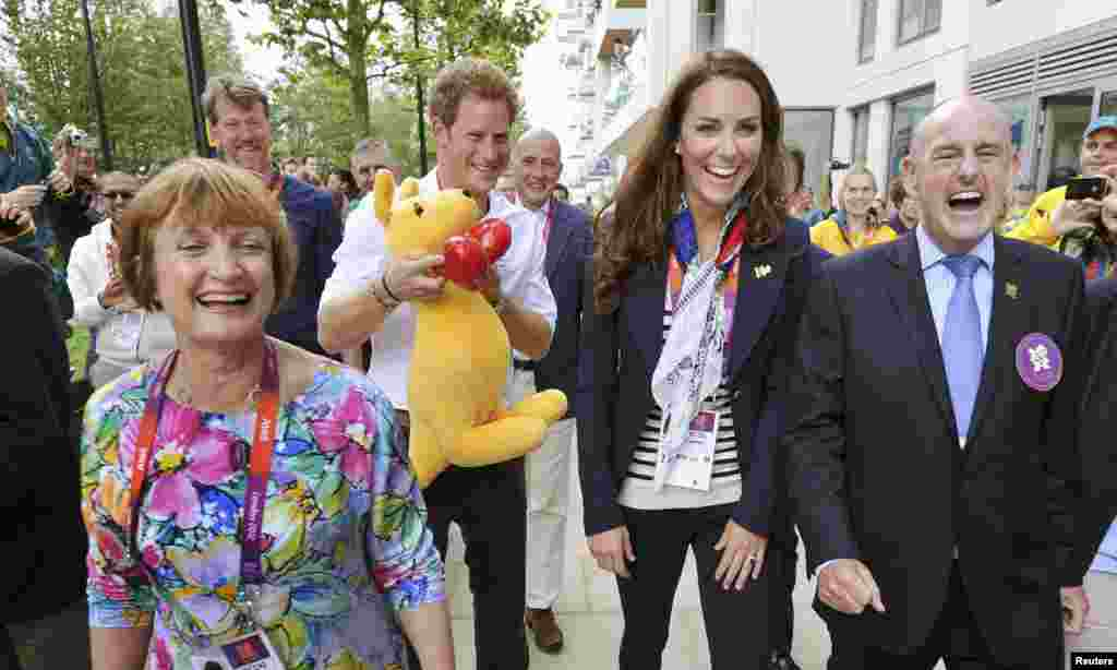 Britain's Prince Harry (2nd L) holds a kangaroo mascot given by Australian athletes next to MP Tessa Jowell (L), Catherine, Duchess of Cambridge and Mayor of the Olympic Village Sir Charles Allen (R), during a visit to the accommodation for British athlet