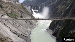 Labors walk on a bridge near the new 450-megawatt hydropower project located at Baglihar Dam on the Chenab river which flows from Indian Kashmir into Pakistan, Oct. 10, 2008.