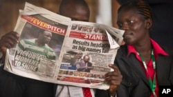 FILE - A Kenyan reads a copy of The Standard newspaper in Nairobi.