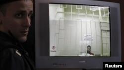 Леонид Развозжаев (на экране монитора) в зале суда
